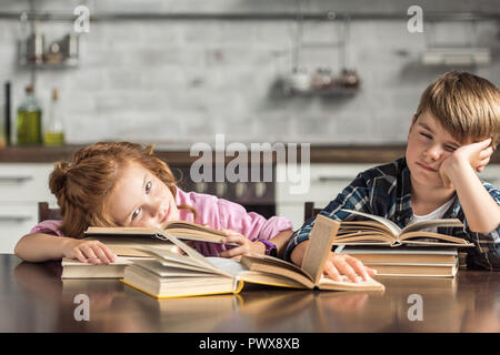 tired little scholars sleeping on book while doing homework Stock Photo