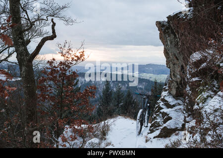 trail covered by snow and a mountain bike. in front of winter landscape on a mountain under a rock. - Stock Photo