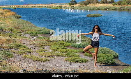 Young girl standing on one leg in front of flamingos - Stock Photo