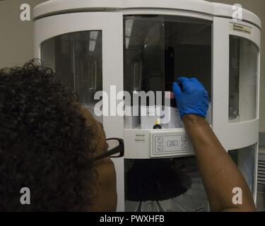 Pamela Baker, 88th Medical Operations Squadron cytology technician, places a rack of cytology slides into the Varistain Gemini, automatic stainer inside the cytology lab at Wright-Patterson Air Force Base Medical Center, June 26, 2017. The automatic stainer maximizes efficiency by organizing histology and cytology staining workflow. - Stock Photo