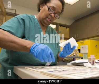 Pamela Baker, 88th Medical Operations Squadron cytology technician, places finished cytology slides to a flat surface for microscopic analysis by a pathologist inside the cytology lab at Wright-Patterson Air Force Base Medical Center, June 26, 2017. A pathologist orders a surgical pathology specimen when a core biopsy has been obtained. - Stock Photo