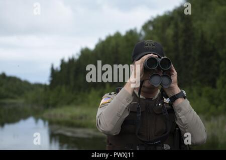 James Wendland, 673d Civil Engineer Squadron chief conservation law enforcement officer, looks off in the distance at a group of nesting loons at Joint Base Elmendorf-Richardson, Alaska, June 30, 2017. Bear encounters have been on the rise this summer at JBER and other Alaska Communities. - Stock Photo
