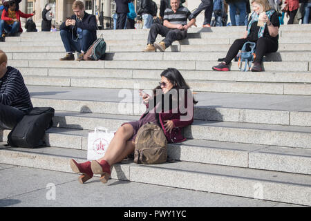 London UK. 18th October 2018. UK Weather: A woman relaxing in the autumn sunshine and warm weather in Trafalgar Square Credit: amer ghazzal/Alamy Live News - Stock Photo