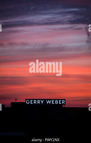 Halle, Germany. 17th Oct, 2018. The emblem of the fashion company Gerry Weber shines in front of the red sky at dusk. The Westphalian textile company continues to struggle with declining sales and expects to be in the red again this year. Credit: Friso Gentsch/dpa/Alamy Live News - Stock Photo