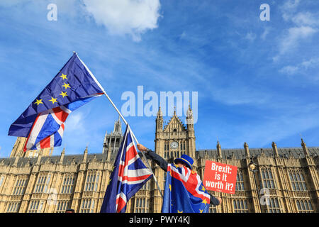 Westminster, London, UK, 18th Oct 2018. Steve Bray, founder of the daily SODEM protest who stands outside Parliament every day in his 'Stop Brexit' hat, shouts and waves flags at passers-by and MP's. A Protester waves flags. Anti-Brexit Protesters from SODEM (Stand of Defiance European Movement) protest outside Parliament, as news breaks that negotiations on a Brexit Deal have once again stalled. Their protest comes ahead of Saturday's planned large 'People's Vote' march in Central London. Credit: Imageplotter News and Sports/Alamy Live News - Stock Photo