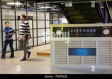 London, UK. 18th Oct, 2018. Amazon employees walk past an oversized radio model in London's Amazon headquarters that promotes the Amazon Music streaming service. At its 'Innovation Day', the Group announced that it would expand its development locations in Europe. (Zu dpa 'Amazon is expanding research and development centers in Europe') Credit: Christoph Dernbach/dpa/Alamy Live News - Stock Photo