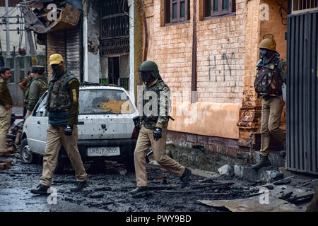 October 17, 2018 - Srinagar, Jammu & Kashmir, - Indian policemen are seen walking past a damaged car outside the house where suspected militants were hiding from during a gun battle.Indian policemen patrol the area after the clashes of the Anti-protest that erupted in the main city in disputed Kashmir after a gun battle between militants and government forces that killed at least two suspected rebels, a civilian and a counterinsurgency police official. Credit: Idrees Abbas/SOPA Images/ZUMA Wire/Alamy Live News - Stock Photo