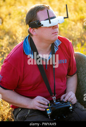 Drone pilot seen wearing a first-person view headset. Young man driving a quad-copter using video-goggles - Stock Photo
