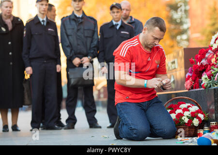 Moscow, Russia. 17th October, 2018. Man lays candels at the WWII Hero Cities Memorial to the city of Kerch in downtown Moscow on October 18, 2018, a day after a 18-year-old student opened fire on his fellow students, leaving at least 21 people dead and dozens injured in a Crimean technical college in Kerch, Crimea. Credit: Victor Vytolskiy/Alamy Live News - Stock Photo