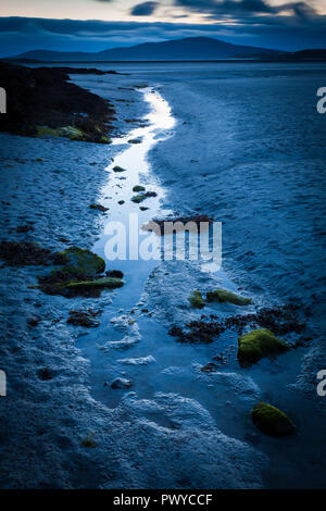 A small stream runs towards the sea over a beach exposed by low tide - Stock Photo