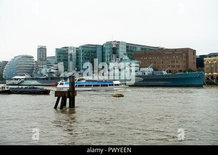 The Famous World War Two Light Cruiser HMS Belfast Moored in the River Thames with a Passing Tourist Boat and the South Bank London England UK - Stock Photo