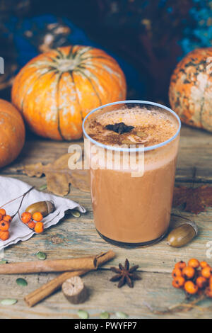 Vegan pumpkin pie smoothie with spices. Healthy fall smoothie recipe: dairy-free smoothie with almond milk, pumpkin puree and banana. Background with  - Stock Photo