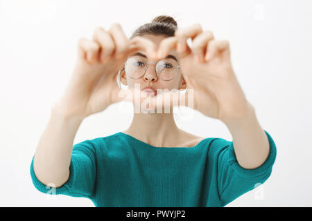 Close-up shot of emotive cute caucasian woman in glasses, pulling hands towards camera and zoom on heart gesture, gazing through hands and folding lips in air kiss, standing tender over grey wall - Stock Photo