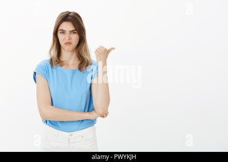 Girl sharing her negative opinion. Portrait of displeased and disgusted attractive european woman, pointing right with thumb, frowning and wrinkling nose, being unimpressed and expressing dislike - Stock Photo