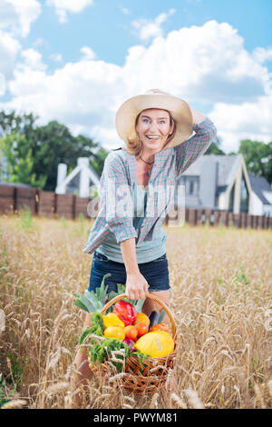Appealing emotional woman feeling happy after harvesting vegetables - Stock Photo