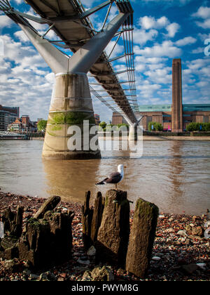 Underneath the Millennium bridge River Thames at low tide, looking towards the Tate Modern - Stock Photo