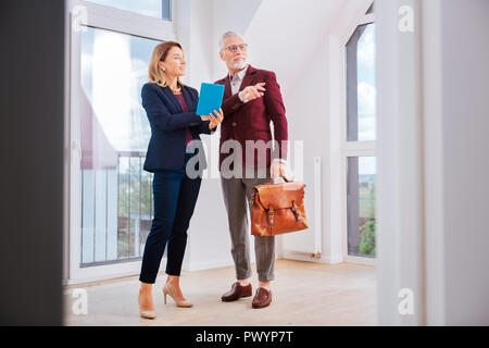 Stylish beautiful estate agent wearing blue costume talking to her client - Stock Photo