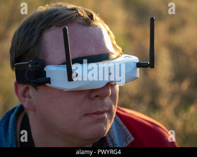 Drone pilot wearing first-person view headset. Young man driving a quad-copter using video-goggles - Stock Photo