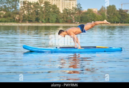 Muscular man practicing yoga, doing balance body weight, swimming on paddle board in middle of city lake, during sunny summer day. Sportsman with perfect figure, wearing blue shorts, training outside. - Stock Photo
