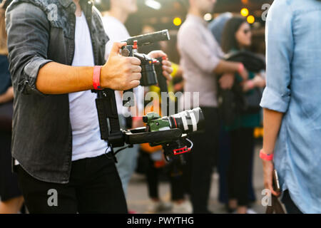 Videographer with gimball video DSLR in an event among people - Stock Photo
