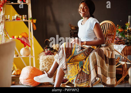 African american girl sitting at rocking chair against
