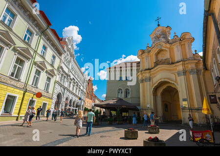 Vilnius old town, view along Didzioji Gatve, a main thoroughfare in the center of Vilnius Old Town, showing the Baroque porch of Holy Trinity Church. - Stock Photo