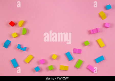 Colorful wooden building blocks on pink background - Stock Photo