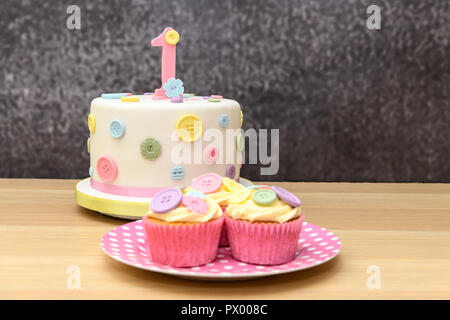 1st Birthday cake with cupcakes, cakepops and biscuits - Stock Photo