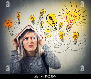 Perplexed young woman holding a opened book over head having many ideas, has to choose the best. Stressed emotion, hard thinking looking at shining li - Stock Photo