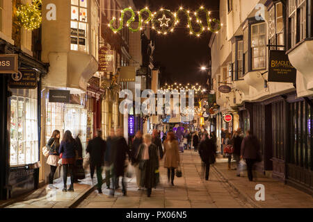 Night time photo of Stonegate in York with Christmas shoppers - Stock Photo