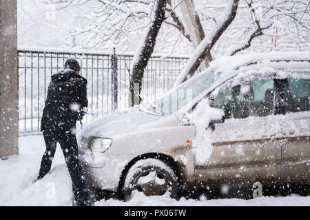 Man in dark clothes cleans his car during heavy snowfall.  - Stock Photo