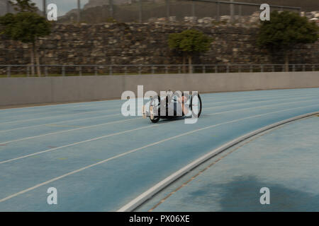 Disabled athlete racing in wheelchair - Stock Photo