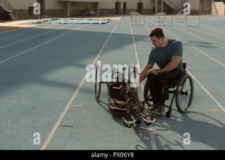 Disabled athletic with wheelchair on a racing track - Stock Photo
