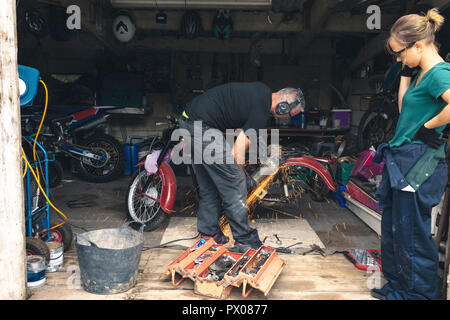 Mechanic using grinder in garage - Stock Photo