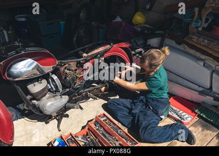 Female mechanic repairing motorbike in garage