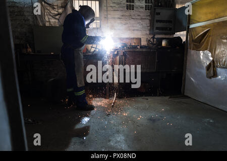 Blacksmith using a welding torch in workshop - Stock Photo