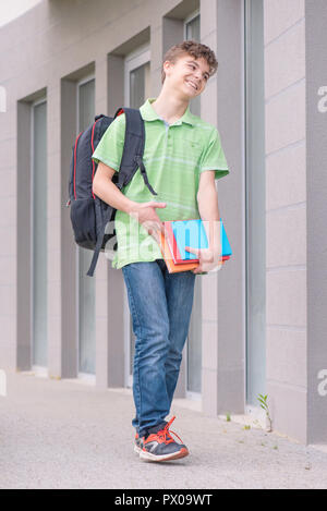 Teen boy 14 years old with backpack and books on the first or last school day. Excited to be back to school after vacation - outdoor. - Stock Photo