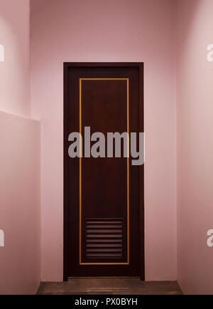 boutique vintage retro wooden door made from plain tropical dark brown textured wood panel board with pink color painted wall background in house. hom - Stock Photo