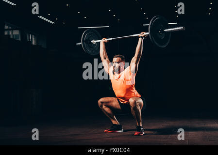 attractive athletic man working out with barbell in dark gym - Stock Photo