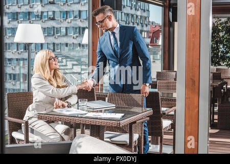 business partners shaking hands during meeting in cafe - Stock Photo