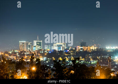 A wide view of Kigali city skyline lit up at night, under a deep blue evening sky with the glow of streetlights in t - Stock Photo