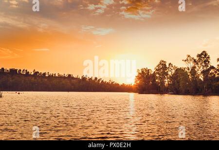 Great sun on the horizon illuminating the lake at sunset - Stock Photo