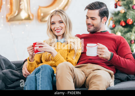 couple holding christmas coffee cups and resting at home together - Stock Photo