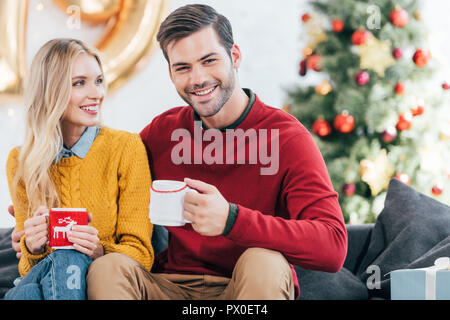 smiling couple with cups of coffee at home on christmas eve - Stock Photo