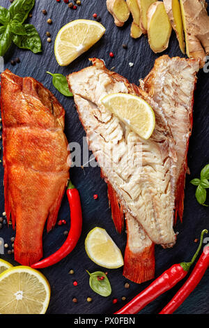 fillet of hot smoked red snapper on a black stone plate with spices, herbs and sliced lemons, vertical view from above, close-up - Stock Photo