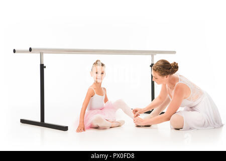 female trainer tying pointe shoes of little ballerina near ballet barre stand isolated on white background - Stock Photo