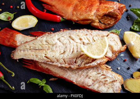 fillet of hot smoked red snapper on a black stone plate with spices, herbs and sliced lemons, view from above, close-up - Stock Photo