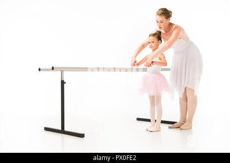 female teacher in tutu helping little ballerina practicing at ballet barre stand isolated on white background - Stock Photo