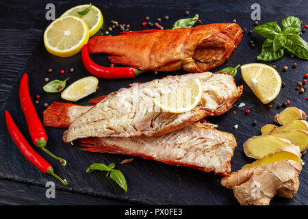 fillet of hot smoked red snapper on a black stone plate with mixed peppercorns, fresh basil leaves and sliced lemons, view from above, close-up - Stock Photo