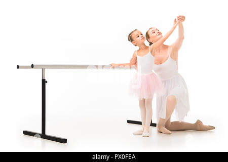 happy female teacher in tutu helping little ballerina exercising at ballet barre stand isolated on white background - Stock Photo